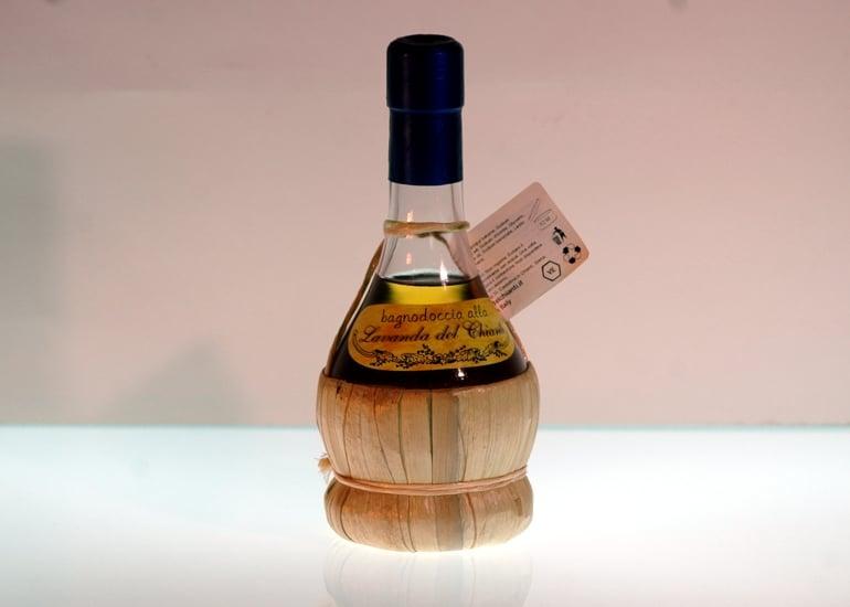 Small flask in chianti wine glass containing lavender shampoo